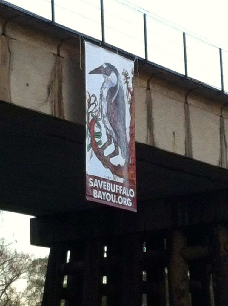 Beautiful banner of a night heron drawn by Houston artist Frank Tolbert hanging over Buffalo Bayou during the annual Regatta.