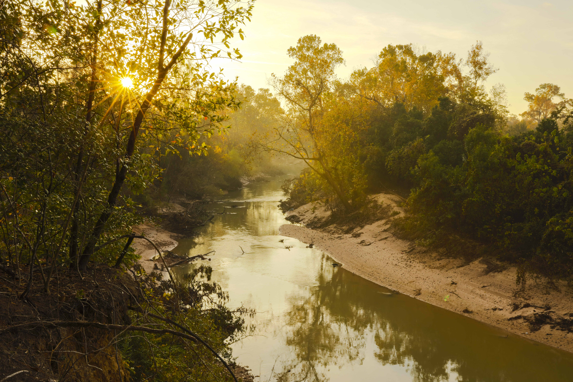 Sun rising over a bend of Buffalo Bayou at low water on Dec. 10, 2015. Photo taken by Jim Olive from a high bluff in Memorial Park looking downstream with the River Oaks Country Club on the right.