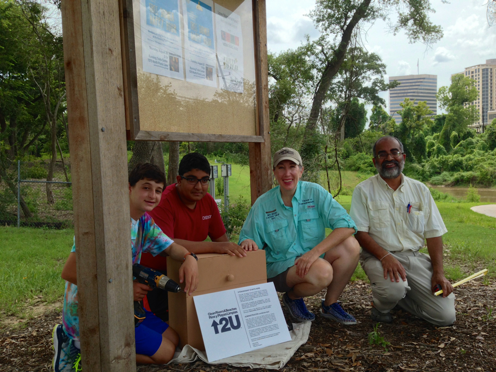 Installing a handbuilt wooden box for reusable mesh bags to collect trash on Buffalo Bayou. At the Woodway boat launch in Memorial Park, part of the Texas Parks and Wildlife Buffalo Bayou Paddling Trail.  From  to right: Boy Scouts Jonah Pesikoff and Saswat Pati, Assistant Scoutmaster Janice Walden, and Boy Scout Dad Debananda Pati.