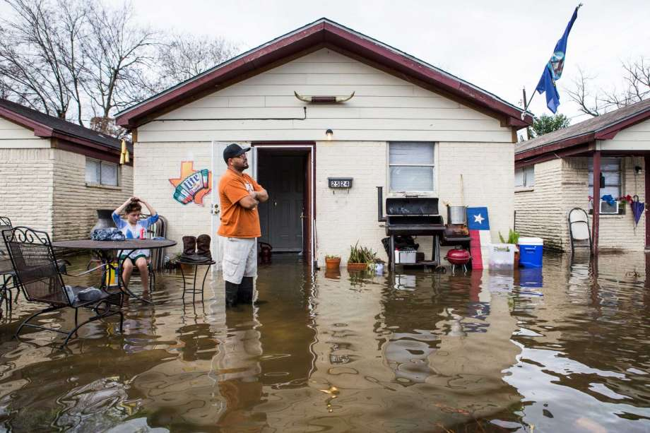 Carlos Gutierrez is calf-deep in water from heavy overnight rains at his house near the 2600 block of Creston on Wednesday, Jan. 18, 2017. Photo for the Houston Chronicle by Brett Coomer.